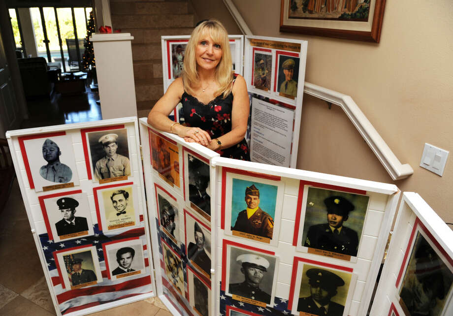 Courtesy Photo Janna Hoehn of Hawaii displays some of the photographs of military personnel whose names are etched on the Vietnam Wall in Washington, D.C. She is part of a group working to collect photos of each one listed on The Wall.