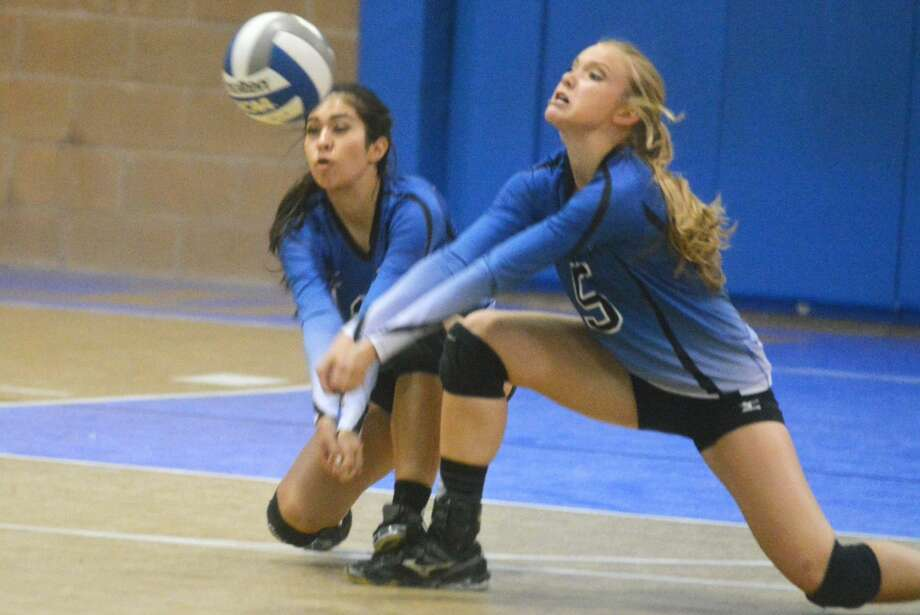 Plainview Christian Academy volleyball players Stephanie Stuckey (right) and Mary Hooton (left) go to a knee to return a Lubbock Home School serve during a match Tuesday night. Photo: Skip Leon/Plainview Herald