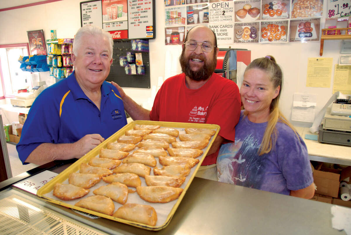Wayland Baptist University Executive Director of Advancement Mike Melcher (left) looks over a tray of fried pies alongside Paul and Patricia Kammerdiener at Mrs. K's Bakery. Mrs. K's, which has been in business in Plainview for 27 years, is donating apple fried pies for the scholarship luncheon featuring former first lady Laura Bush on Oct. 21.