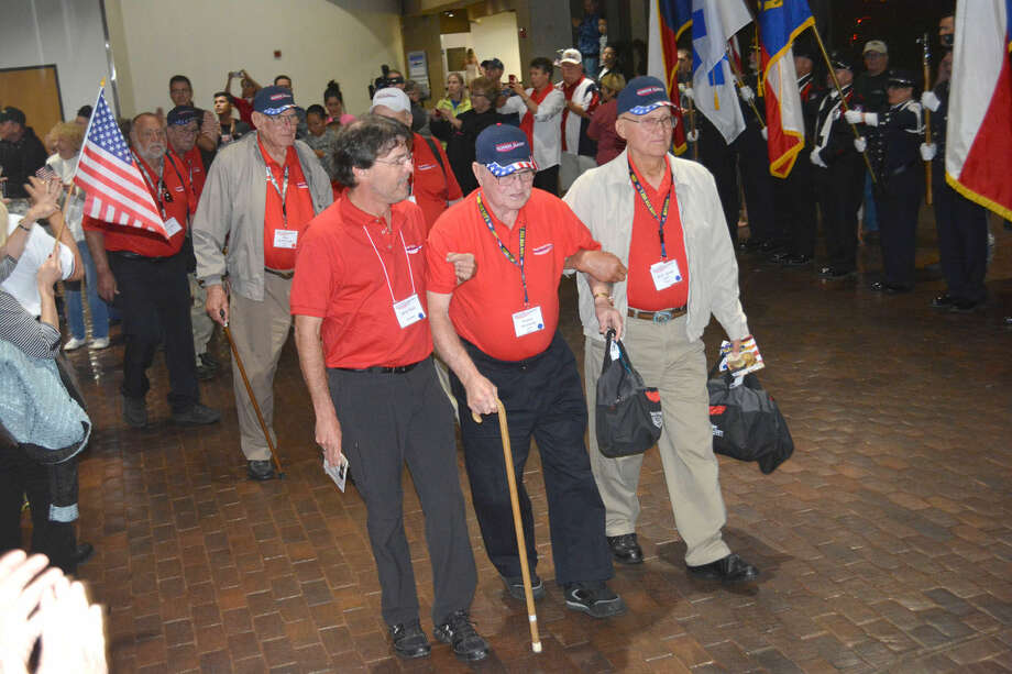 Veterans return homeDoug McDonough/Plainview HeraldAfter a three-day visit to the nation's capital, the South Plains Honor Flight returned home late Friday night to the Lubbock airport and were greeted by a brass band, bagpipers, military and first responder honor guards and a huge crush of flag waving relatives and well-wishers. Ninety World War II, Korean and Vietnam war veterans from across the South Plains along with their guardians and others made the trip to visit the World War II, Korean War and Vietnam War memorials and other landmarks in Washington, D.C. Assisting WWII Navy veteran Huston Hunnicutt as he walks through the crowd of well-wishers Friday night are guardian Jerry Koch (left) and fellow WWII Navy veteran R.D. Jones, followed by WWII Army veteran John McDonough and his son Mike. In addition to the McDonoughs, others from Plainview on this year's Honor Flight were veterans Berl Reagan and Bo Blankenship, and Randy Faulkenburg who served as a guardian.