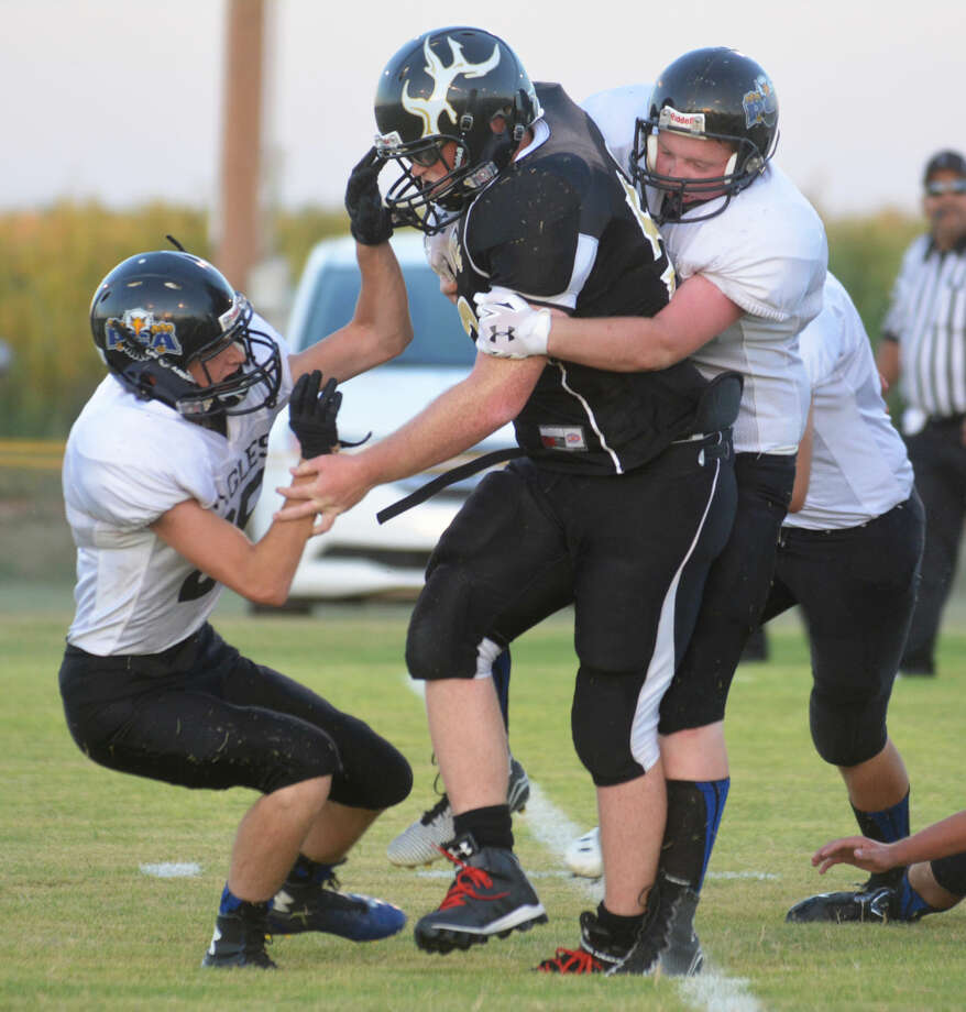 Cotton Center's Austin Barrow bulls his way for yardage as Plainview Christian Academy defenders Luke Brown (right) and J.W. Jackson (left) try to bring him down. Photo: Skip Leon/Plainview Herald