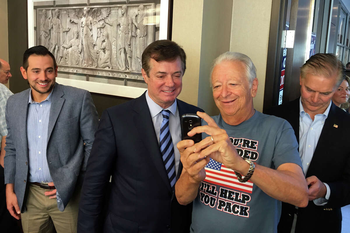 Trump campaign manager Paul Manafort, center, takes a selfie with former Norwalk mayor and current Ridgefield resident Richard Moccia during a Connecticut GOP breakfast .