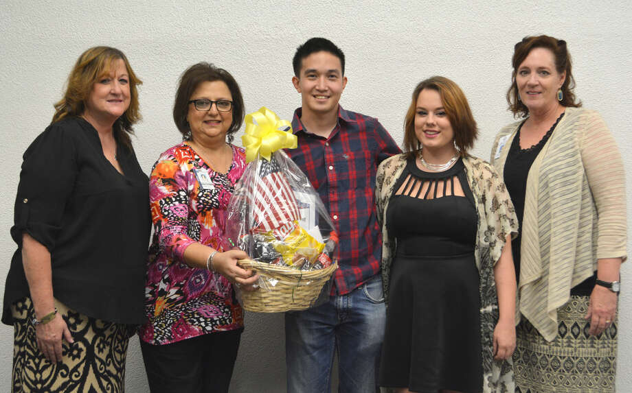 Marine veteran Brian Tran and wife Kayla (center) hold a gift basket from Runningwater Draw RSVP, presented by Angie Nelms (left), Military Veteran Peer Network; Irma Shackelford, RSVP executive director; and Karla Glowicki, county veteran service officer.