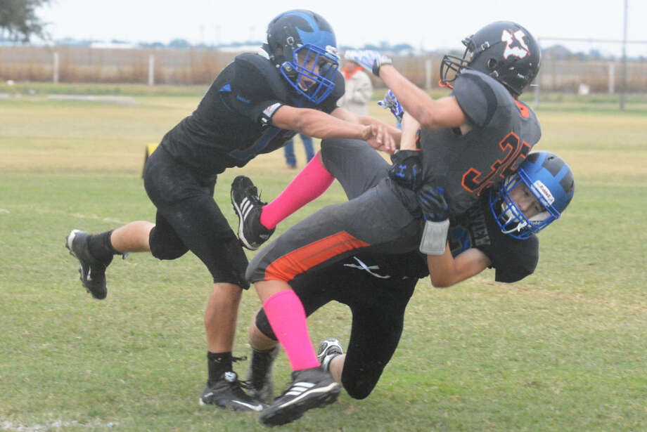 A pair of Plainview Christian Academy defenders lift the Lazbuddie quarterback into the air as they tackle him just after he passed the ball during PCA's homecoming game Friday. Photo: Skip Leon/Plainview Herald