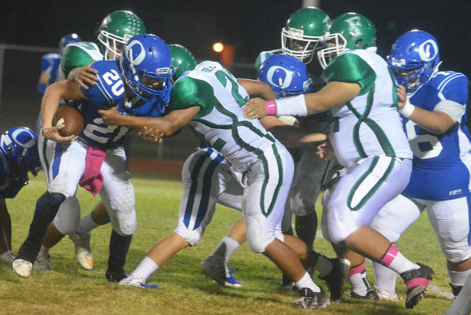 Floydada defenders Miguel Pena (back) and Albert Dehoyos (22) team up to tackle Olton quarterback T.J. McCall (20) during a District 2-2A football game in Olton Friday night. Photo: Skip Leon/Plainview Herald