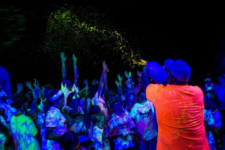 Participants in a summer UV Splash Color Dash get doused under the black lights of the event. Photo: Courtesy Photo