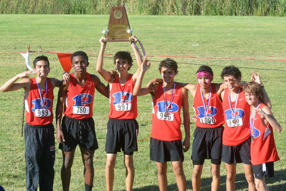 The Plainview Bulldog cross-country team celebrates their third consecutive District 4-5A championship at Mae Simmons Park in Lubbock Thursday. Team members are, from left, Josue Hernandez, Michael Perry, Ricardo Flores (holding trophy), Luis Castro, Sergio Lara, Roy Acosta and Hunter Thomas. Photo: Skip Leon/Plainview Herald