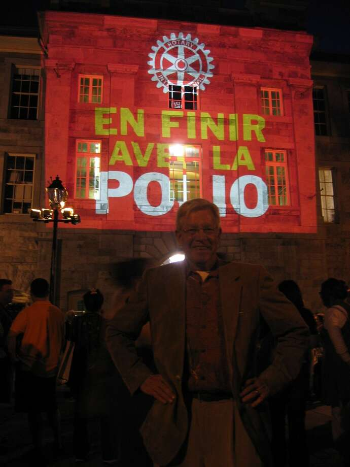 """Courtesy PhotoRotarian Charles Starnes stands in front of the """"End Polio Now"""" banner displayed in French at the Montreal Rotary International Convention in 2010. Rotary announced that India was on the verge of being polio free, a feat realized less than one year later."""