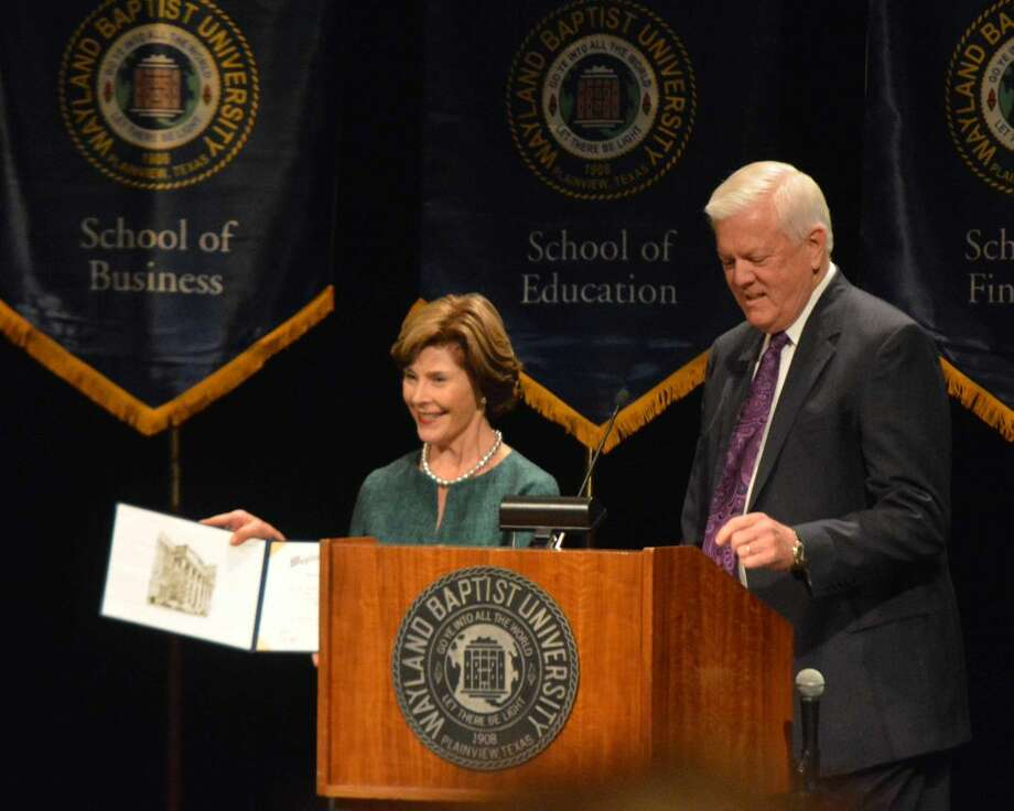 Former first lady Laura Bush displays her honorary Doctor of Letters degree from Wayland Baptist University which she received moments earlier from WBU President Dr. Paul Armes during chapel on Wednesday. Wife of the 43rd U.S. president, Bush was on campus as featured Willson Lectures Series speaker.