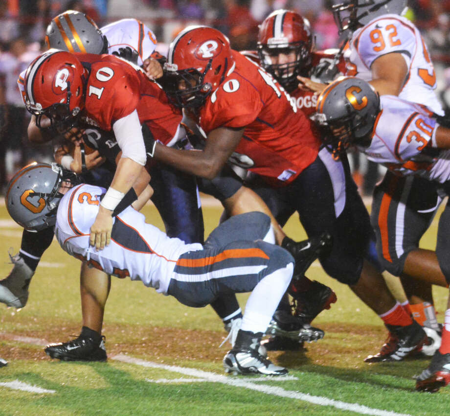 Plainview quarterback Paxstyn Oldfield (10) runs over Caprock defender Ezequiel Tenorio (2) with some help from teammate Crystin Baston (70) during the Bulldogs' 39-22 Homecoming victory over the Longhorns Friday night. Photo: Skip Leon/Plainview Herald