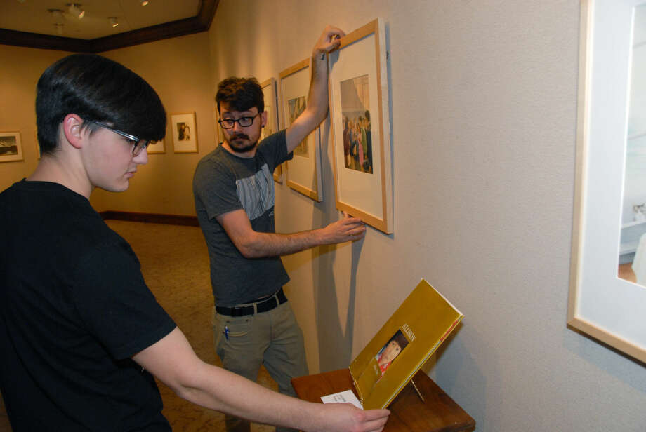 """Jonathan Petty/Wayland Baptist UniversityWayland art students Justus Brozek, left, and Jon Riddle prepare the Abraham Art Gallery for the new show """"Journey of Memory: Works of Allen Say"""" that opens Monday, Nov. 2."""