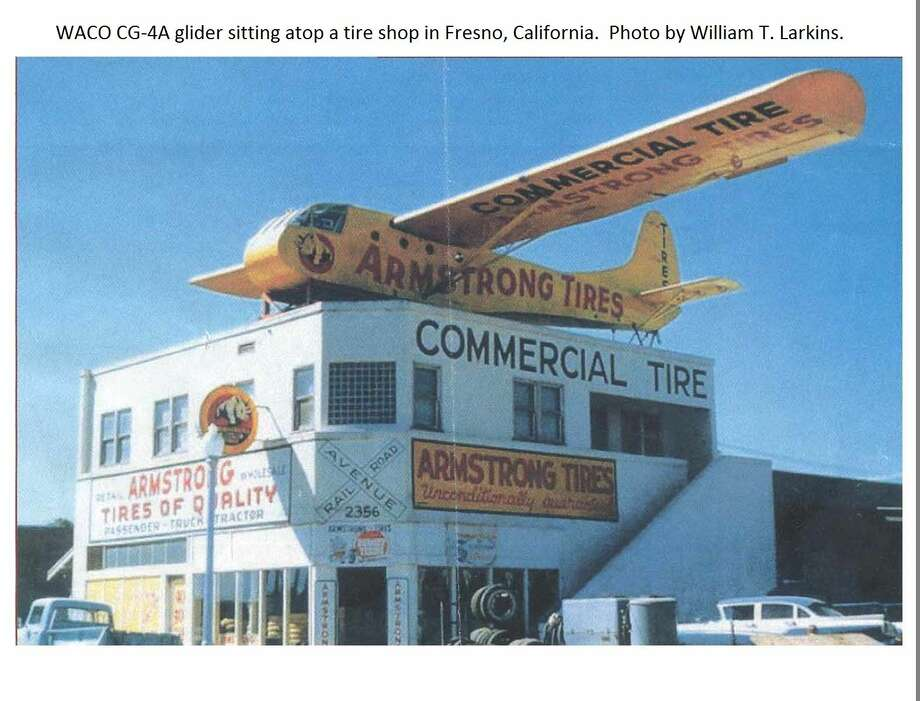 A 1950s photo taken by William T. Larkins shows a retired WWII-era WACO CG4A glider used as a rooftop advertisement for a tire shop in Fresno, California.