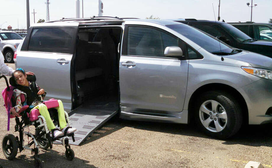 Ten-year-old Noemi Garcia stands next to a new wheelchair accessible van which was donated to her family by an anonymous individual.