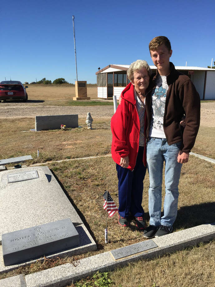James Doucette/Courtesy Photo Eagle Scout candidate Jake A. Moore of Lockney joins Norma Ragland in Lockney Cemetery next to the grave of her husband, Homer Ragland Jr. Moore choose as his Eagle service project to install flag holders at the graves of veterans buried in Lockney Cemetery, including Ragland who served in the U.S. Navy during World War II.