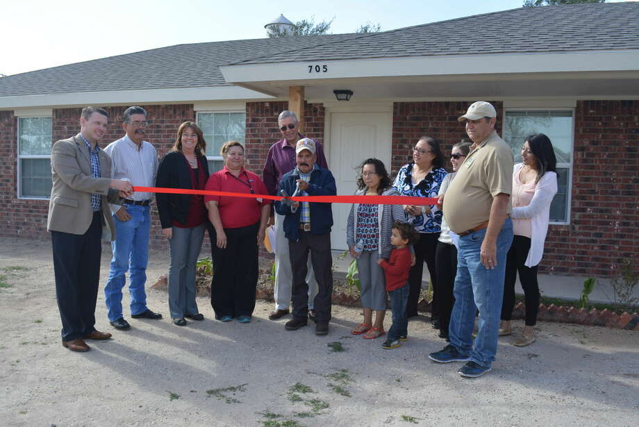 In one of four special key ceremonies Thursday, homeowner Serafin Saucedo cuts the ribbon to his newly constructed home alongside City of Plainview and SPAG representatives and family. Photo: Homer Marquez/Plainview Herald