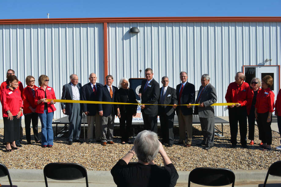Doug McDonough/Plainview Herald Surrounded by college regents and other officials, South Plains College President Dr. Kelvin Sharp clips a ribbon Friday morning to formally open the Plainview Technology Center. Adjacent to the SPC Plainview Center at 1920 W. 24th, the $1.2 million facility expands the school's workforce training capacity.