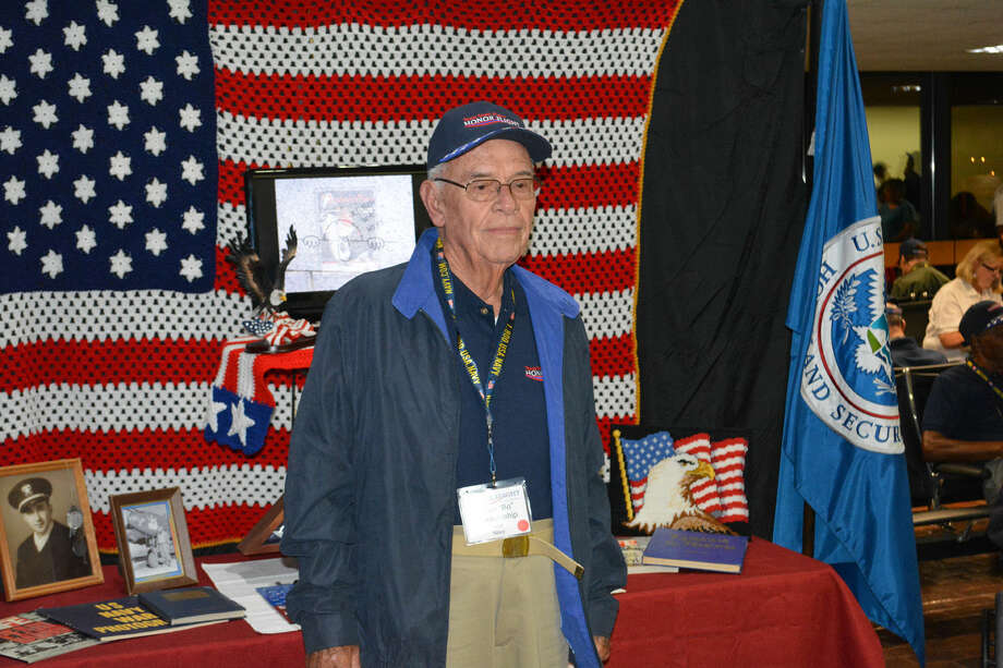 Longtime Plainview resident Bo Blankenship, a U.S. Navy veteran from the Korean War, is among about 90 military veterans participating in the 2014 South Plains Honor Flight which departed from Lubbock early Wednesday. He poses in front of a display table while waiting to board the flight. Blankenship moved from Plainview to Marble Falls earlier this year.