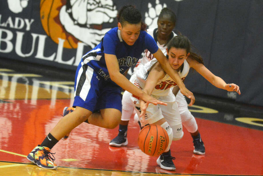 Plainview's Amela Dizdarevic (right) battles with a Lubbock Titans player for possession of the ball during the Lady Bulldogs' opening game of the season Thursday night. Photo: Skip Leon/Plainview Herald
