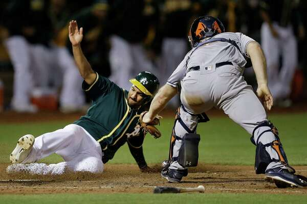 Oakland Athletics' Marcus Semien, left, slides to score past Houston Astros catcher Evan Gattis in the tenth inning of a baseball game Tuesday, July 19, 2016, in Oakland, Calif. Semien scored on a hit by Josh Reddick. (AP Photo/Ben Margot)