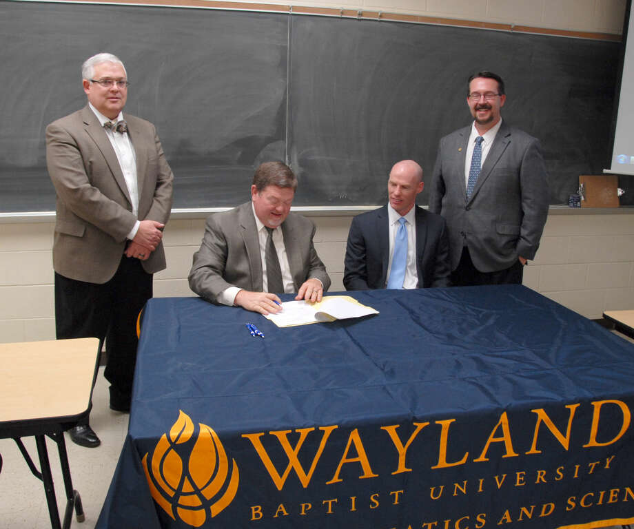 Wayland Baptist University Associate Vice President Dr. Stan Demerritt (standing, left) and Dean of the School of Mathematics and Sciences Dr. Scott Franklin (right) look on as WBU Executive Vice President and Provost Dr. Bobby Hall and West Texas A&M University Associate Dean of the School of Engineering Dr. Matt Jackson sign an agreement between the schools that will make it possible for students to earn dual degrees in math and engineering.