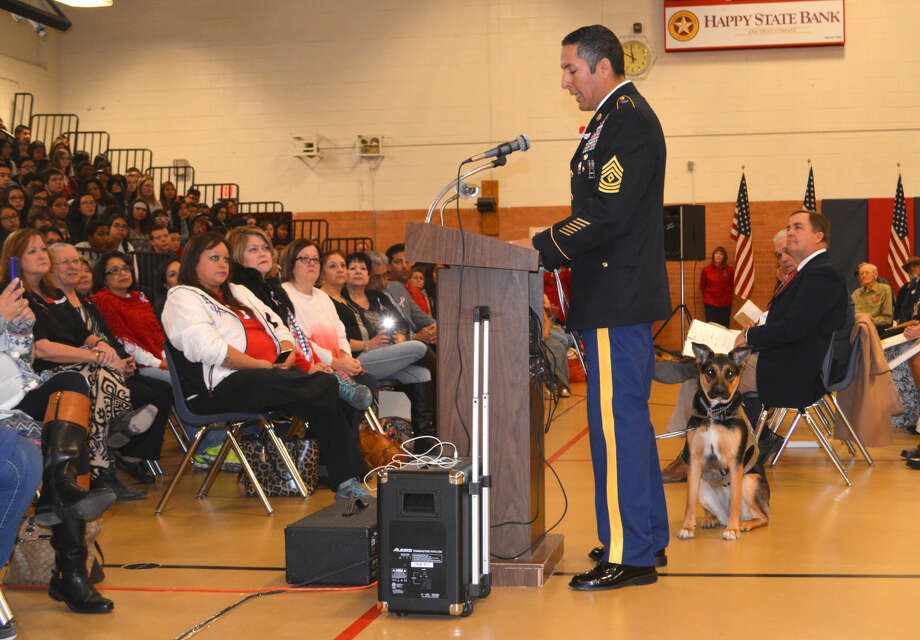 As retired First Sgt. Felipe Azua speaks to eighth graders Wednesday during the annual middle schools' Veterans Day tribute, his service dog Zoey remains vigilant. The therapy canine has been Azua's companion for the past year.