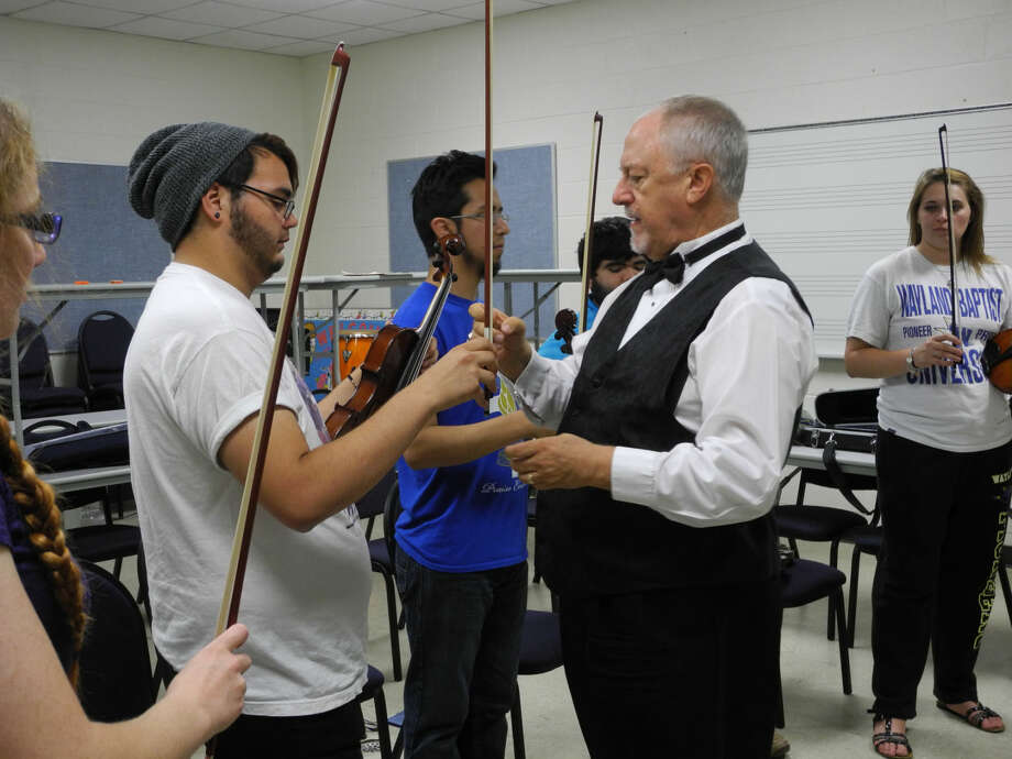 Boyce Wyrick, conductor for Plainview Symphony Orchestra, shows future music teachers the proper positioning of a bow in a recent class at WBU. Wyrick will conduct Plainview Symphony's first concert of the season at 7:30 p.m. Thursday, Oct. 9, in Harral Auditorium. The concert will benefit the American Heart Association. Photo: Gail M. Williams | Plainview Herald