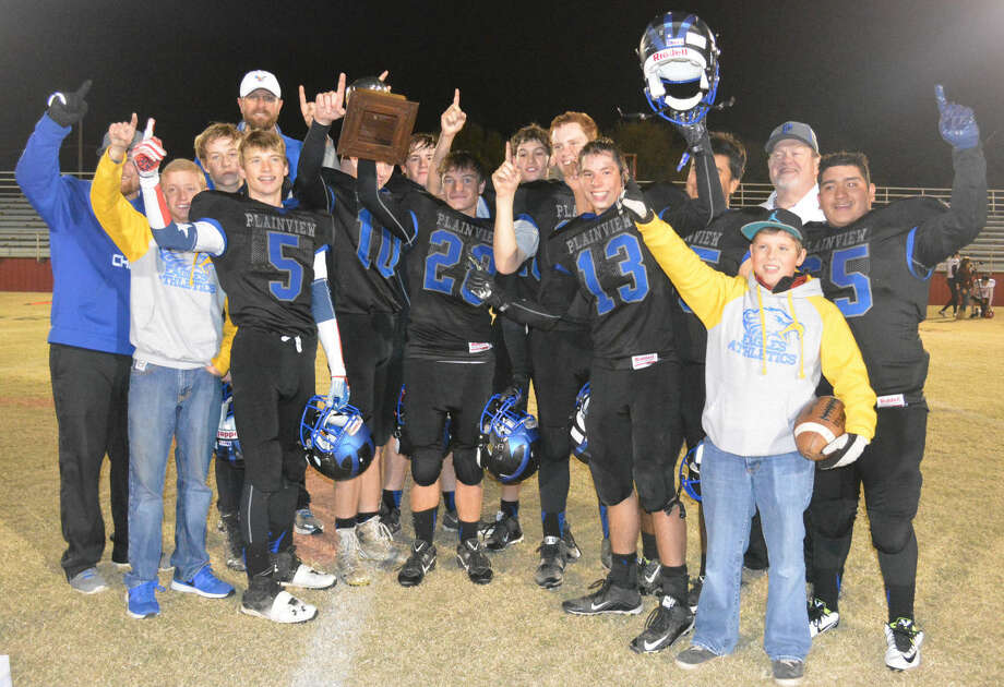 The Plainview Christian Academy Eagles pose with the gold football they earned for winning the TAPPS Class 2A bi-district championship Saturday night. It was the first football playoff game in school history and the first gold football for the school's trophy case. Photo: Skip Leon/Plainview Herald