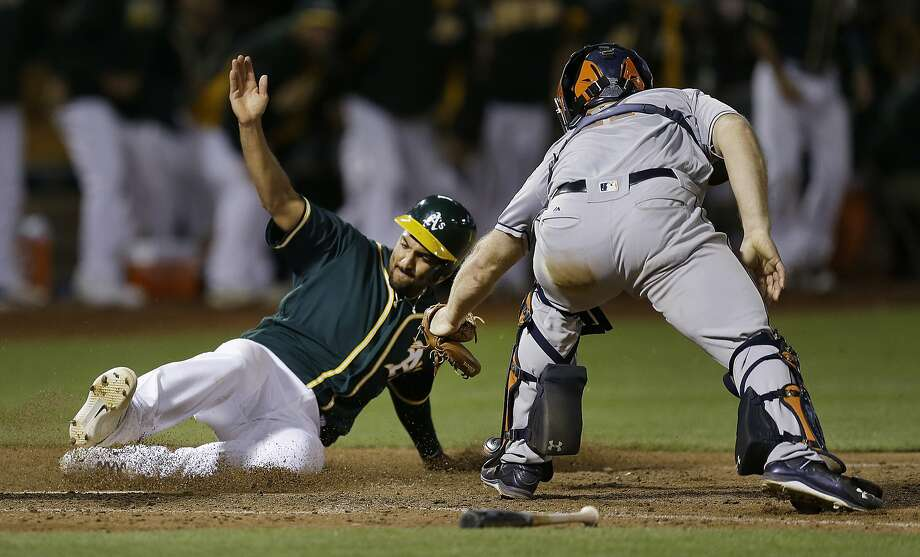 Oakland Athletics' Marcus Semien, left, slides to score past Houston Astros catcher Evan Gattis in the tenth inning of a baseball game Tuesday, July 19, 2016, in Oakland, Calif. Semien scored on a hit by Josh Reddick. (AP Photo/Ben Margot) Photo: Ben Margot, Associated Press