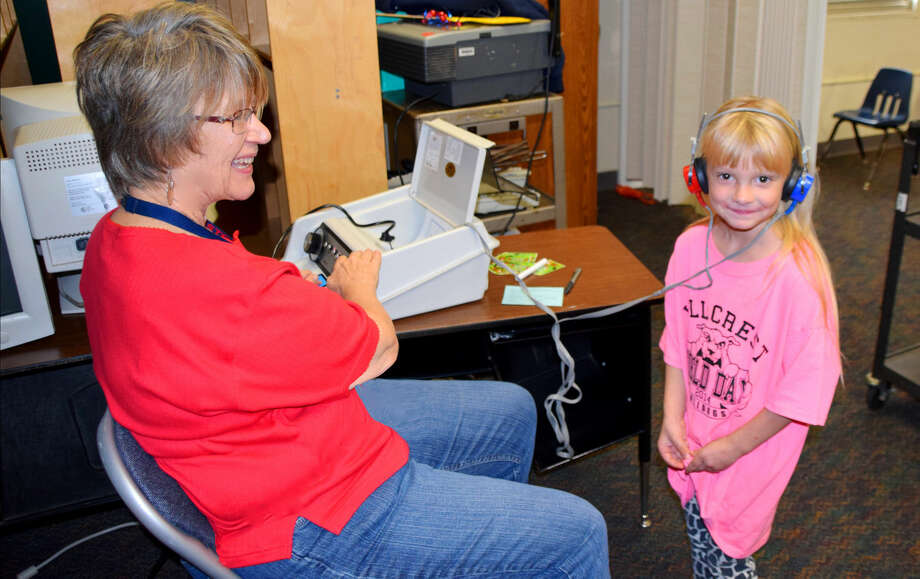 Jan Seago/Plainview ISDSchool nurse Nancy Cox conducts a hearing screening on Hillcrest kindergarten student Violet Roberts. School nurses are trained and certified to conduct the vision and hearing screenings that are required by state code for students enrolled in public or private schools in Texas.