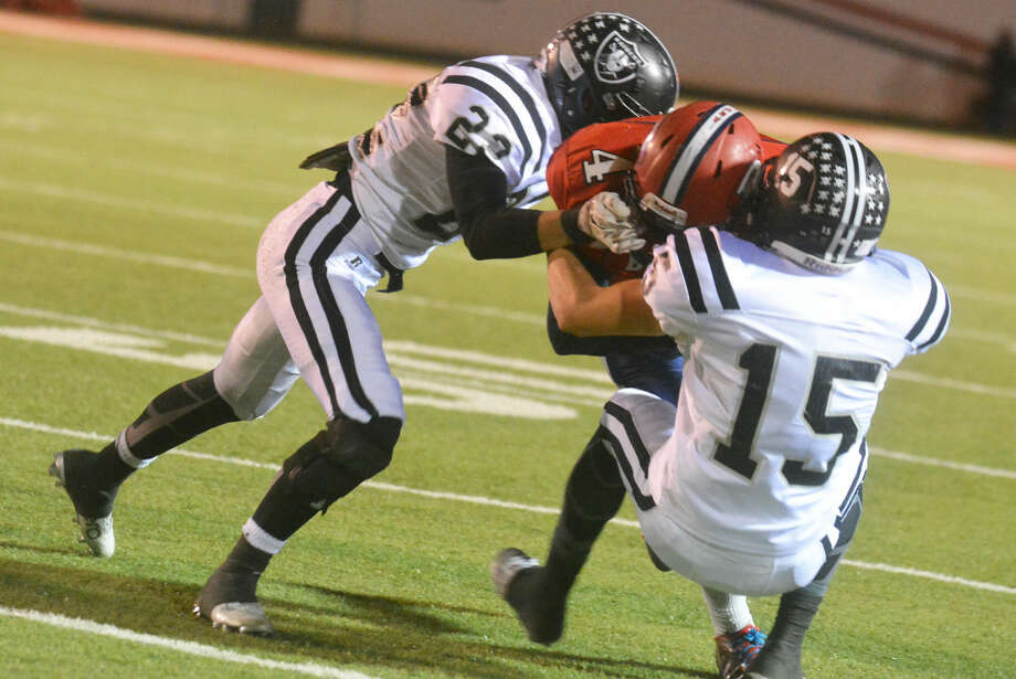 Plainview running back Trendan Jackson (4) is tackled by two Randall players during a bi-district playoff game earlier this month. The Bulldogs have been to the playoffs two years in a row. They could face a bit more of a challenge next season if Lubbock Monterey and Lubbock Coronado drop to 5A and enter the district. Photo: Skip Leon/Plainview Herald