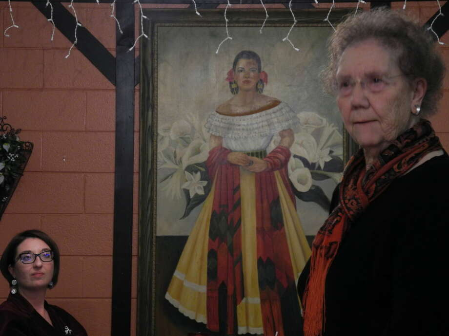 June Wells introduces a speaker at the annual Hi-Plains Genealogy Society/Hale County Historical Commission joint meeting at Old Mexico. In the background is a portrait of Josephine Valenguela's housekeeper, painted by art teacher Daphne Hegi. Valenguela was the original wner of Old Mexico.