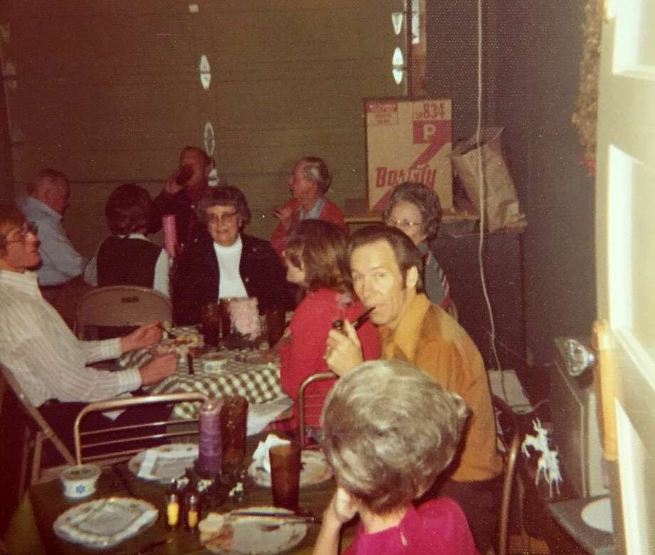 A typical Wall Christmas breakfast with tables set up in the garage. Phyllis Wall's father John Dayton, sitting next to her mother Lorena Dayton, looks at the camera. Christmas I Remember