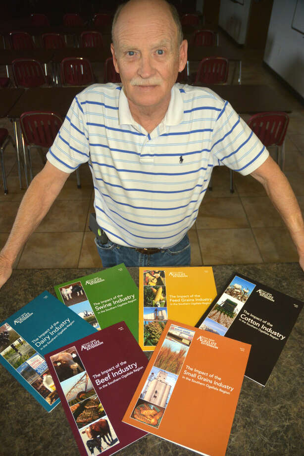 Kay Ledbetter/Texas A&M AgriLife Communications Dr. Steve Amosson, Texas A&M AgriLife Extension Service economist, shows off the six new publications outlining agriculture use of the Ogallala Aquifer in the Southern High Plains.