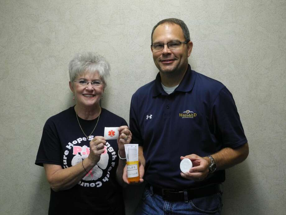Andrea Ingram and Kevin Lewis, vice president of the Kiwanis, hold up a Vial of Life and a sticker that alerts medical personnel that your vital information is in a vial in your refrigerator. Photo: Gail M. Williams | Plainview Herald