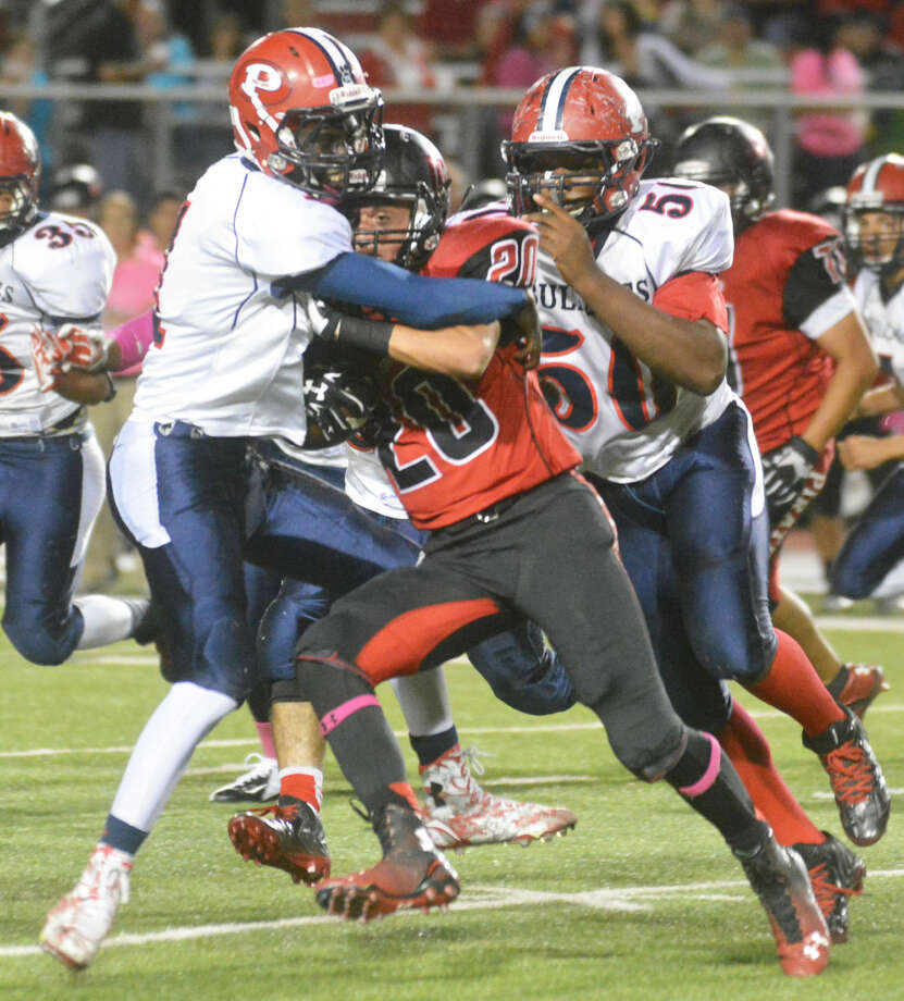 Plainview's Quenion Hines wraps up Lubbock Cooper running back Seth Watts as teammate Roy Abanonu (50) closes in to help out. Photo: Skip Leon/Plainview Herald