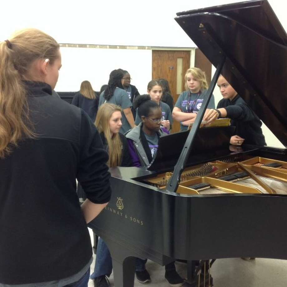 Jonathan Petty/Wayland Baptist University Several girls from the Talkington School for Young Women Leaders gather around one of Wayland's Steinway and Sons grand pianos in the recital hall. The students were on campus Monday to tour the School of Music as well as practice for a recital they were performing later in the day.