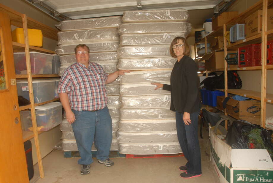 Owner of Jimmie Dan Company's Mattress Mini Warehouse, JohnMark Spruill, left, donates 25 beds to the safe house of the Crisis Center of the Plains. Photo: Homer Marquez/Plainview Herald