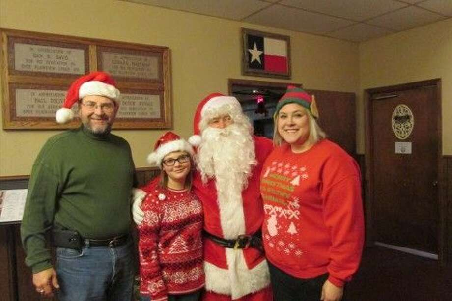 Jana Cannon/Plainview Elks Santa Claus (brought to life by Ralph Langley) poses with Charles Lawson and daughters Kristin and Kaitlin during the Plainview Elks' recent Cowboy Christmas for Seniors lunch. Charles and Kaitlin sang Christmas carols as entertainment during the event. For clients of Meals on Wheels, the Salvation Army and Hale County Senior Citizens, meals were delivered to 114 with 80 served at the lodge.
