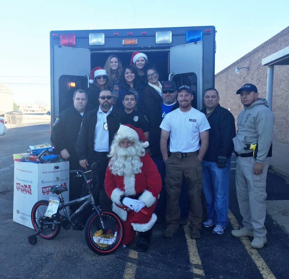 On Wednesday, the Plainview Police Department and community donations helped to kick off the second annual Christmas for Kids program. Loading up toys for kids in the back of the department's SWAT vehicle, Santa, members of the Elks' Lodge and Plainview police distributed gifts around Plainview. Photo: Homer Marquez/Plainview Herald