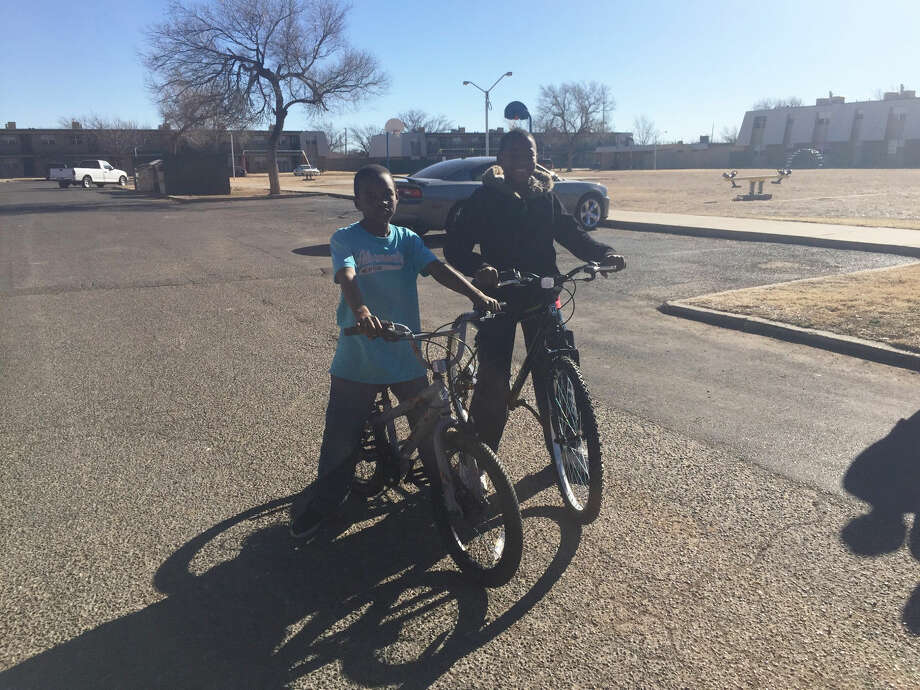 Zaeqwon Riddley, 11, and Brelyn Riddley, 8, who live at the Central Village Apartments in Plainview, show their new bikes, given as a gift by television personality Todrick Hall. Photo: Homer Marquez/Plainview Herald