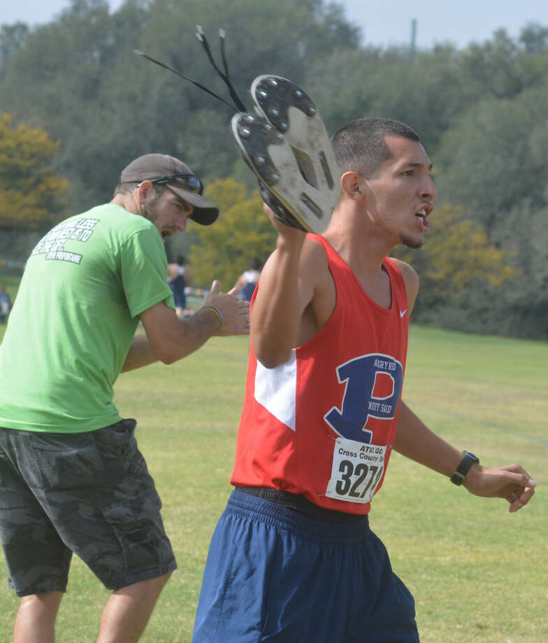 Plainview cross country coach Tim McCune (left) and top boys runner Jarel Rosas (right) cheer on junior varsity runners at the district meet last week. Rosas finished 11th individually at the regional meet Friday to lead the Plainview boys team to the state meet for the first time in school history. Photo: Skip Leon/Plainview Herald