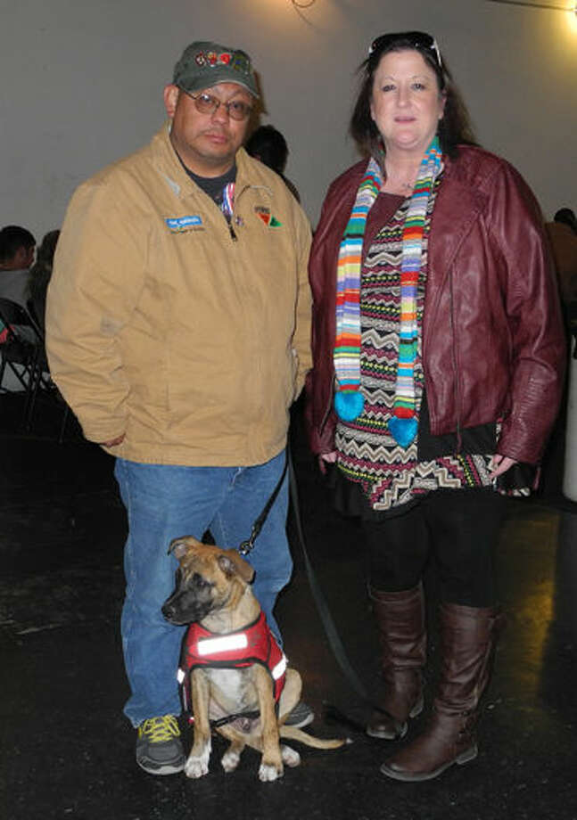 Angie Nelms, volunteer coordinator for Military Veteran Peer Network, stands with Henry Hernandez and his dog Sargent at the veterans luncheon at Thirsty's on Tuesday. Sargent helps the veteran of more than 10 years cope with PTSD. Photo: Gail M. Williams | Plainview Herald