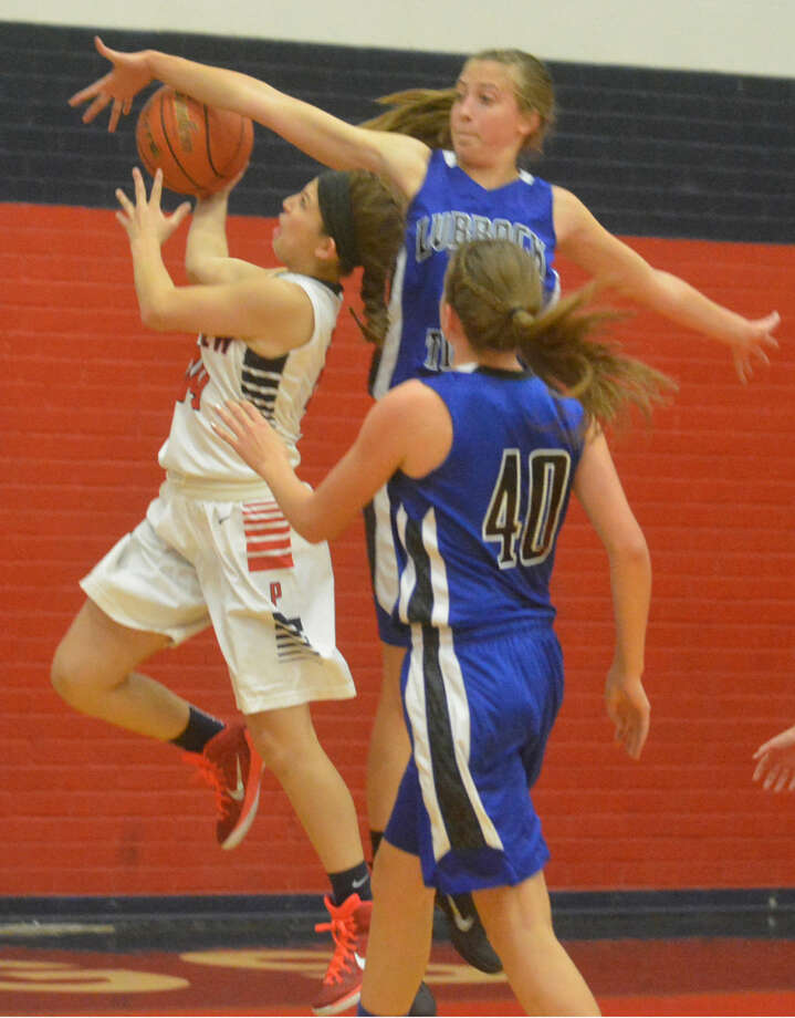 Plainview's Karly Sanchez drives to the basket against Lubbock Home School Thursday night. Sanchez ignited a Lady Bulldog rally with a rare four-point play late in the third quarter to help her team overcome a 23-point deficit and post a 61-54 victory in their first game of the season. Photo: Skip Leon/Plainview Herald
