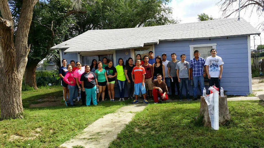 Above, members of the Our Lady of Guadalupe confirmation class stand next to a recently painted home. The group volunteered to paint and clean two houses this past September. Photo: Courtesy Photo