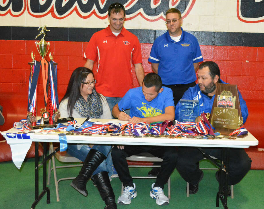 Plainview distance runner Jarel Rosas (seated, center) signs a letter of intent Monday to run cross country and track at Wayland Baptist University next year. Flanking Rosas are his mom, Elena Azua (left), and his dad, Rene Rosas (right). Standing behind Rosas are Plainview High School cross country coach Tim McCune (left) and Wayland Baptist cross country coach Brian Whitlock (right). Photo: Skip Leon/Plainview Herald