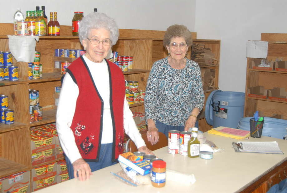 FISH volunteers Audrey Hooper and Margret Saul help to fill baskets for those in need. Photo:  Homer Marquez/Plainview Herald