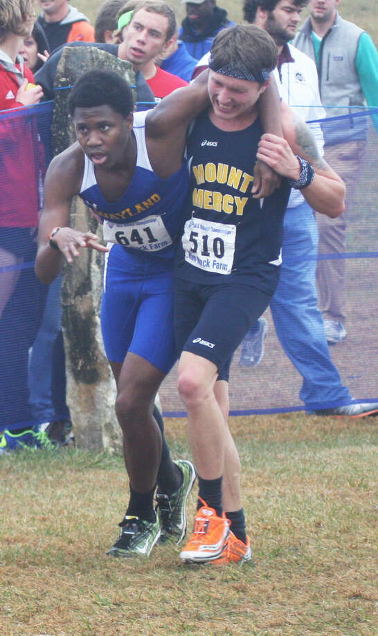 Tyler Keith of Mount Mercy University (Iowa) assists Wayland Baptist runner Cameron Woodberry after Woodberry collapsed just short of the finish line at the NAIA Men's Cross Country National Championships in Kansas. Photo: Photo By Robert J. Lopez