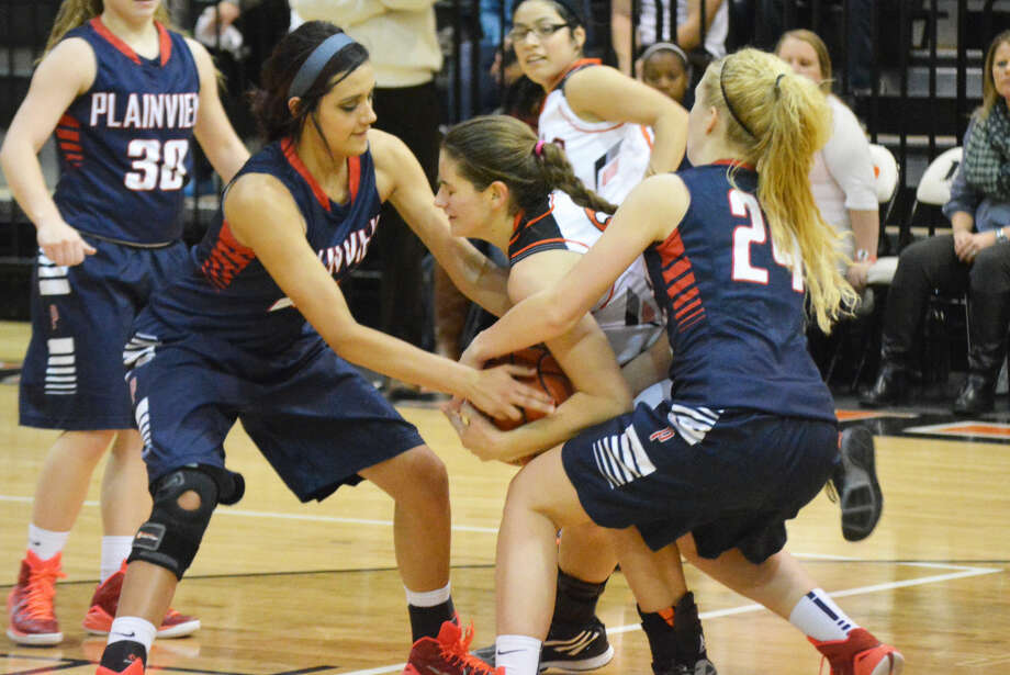 Plainview's Harlee Davis (left) and Allie Bennett (right) try to wrestle the ball away from a Dumas player during a game earlier this week. The Lady Bulldogs beat El Paso Eastlake at the Levelland Tournament Friday. Photo: Doug McDonough/Plainview Herald
