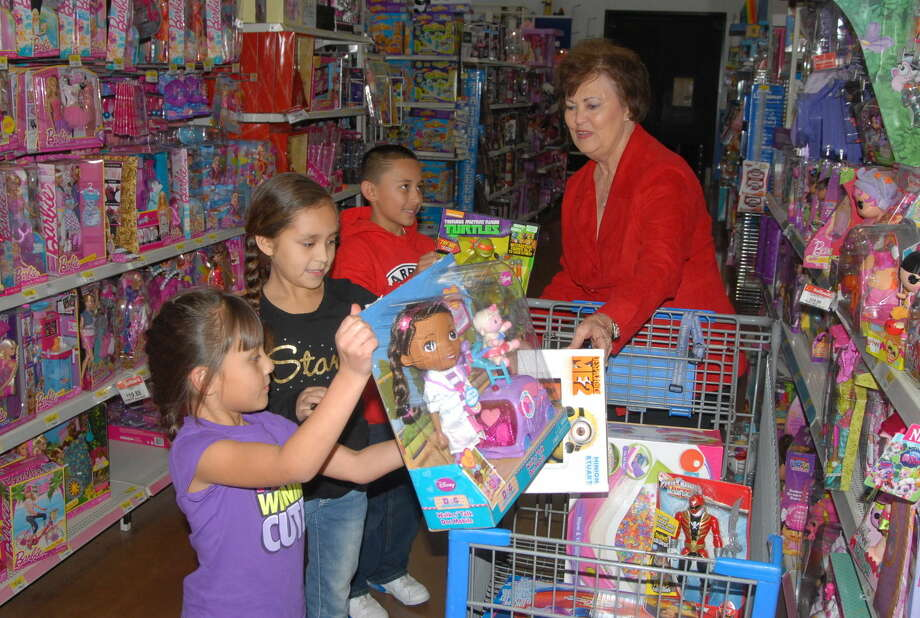 Aubrie Rogers and Layla Juarez fill up the shopping cart, while Devin Rogers hands Crisis Center of the Plains director Kay Harris a brand new toy during a Christmas shopping spree that will benefit the center. Photo: Homer Marquez/Plainview Herald
