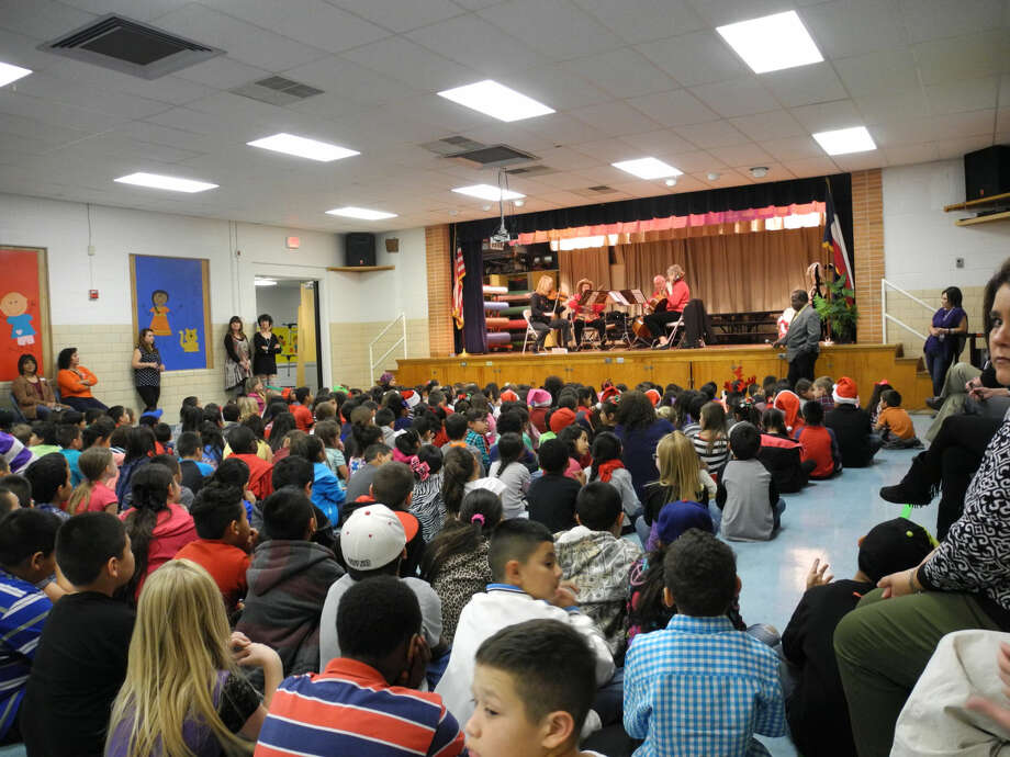 A string quartet from the Plainview Symphony Orchestra played holiday music for about 420 children, grades pre-K-5, in the school cafeteria at Hillcrest Elementary School Wednesday. Photo: GAIL M. WILLIAMS | PLAINVIEW HERALD